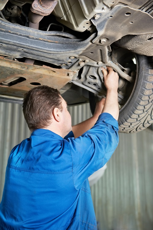 a mechanic checking a car's suspension